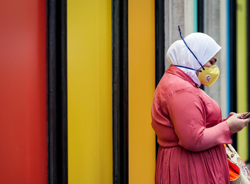 Photograph of woman wearing mask looking at mobile phone